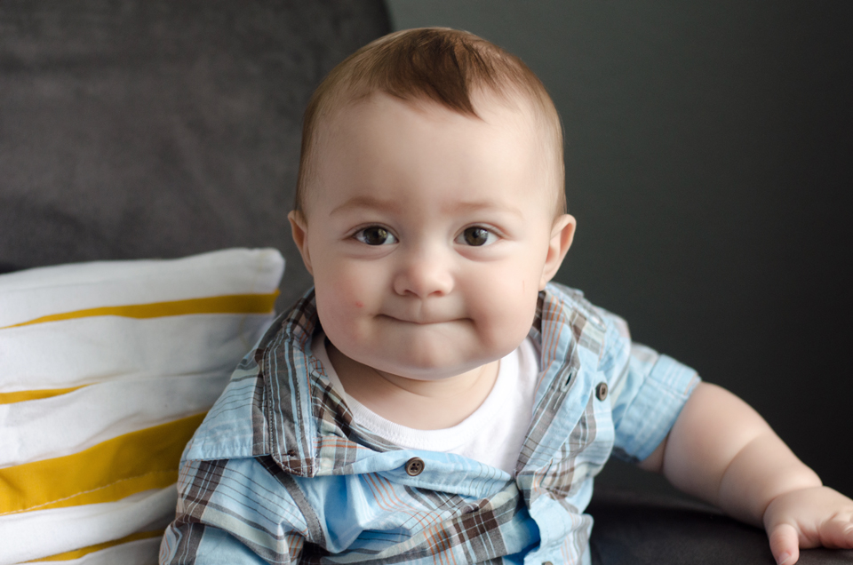 Miles - 9 Month baby photos - On his grey chair looking up at me with a grin
