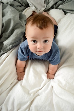 Miles - 9 Month baby photos - Looking up at me while he tries to crawl on the bed