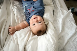Miles - 9 Month baby photos - Laying on the bed and looking up at me