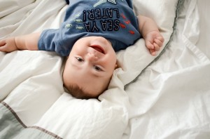 Miles - 9 Month baby photos - Laying on the bed while he looks back and laughs at me