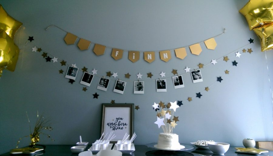 A wide shot of the cake table including the banners and garlands above and the gold star balloons on either end