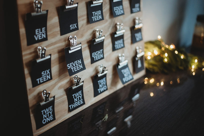 closeup of black advent activity cards arranged on a wooden board - advent calendar design